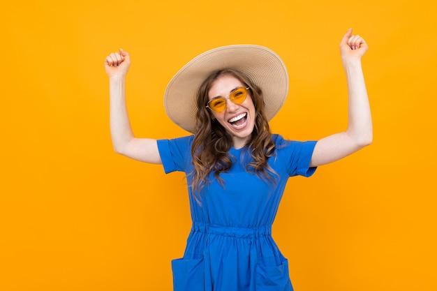 Emocional mujer de mediana edad de pelo castaño en un sombrero y vestido azul sobre un fondo de pared amarilla