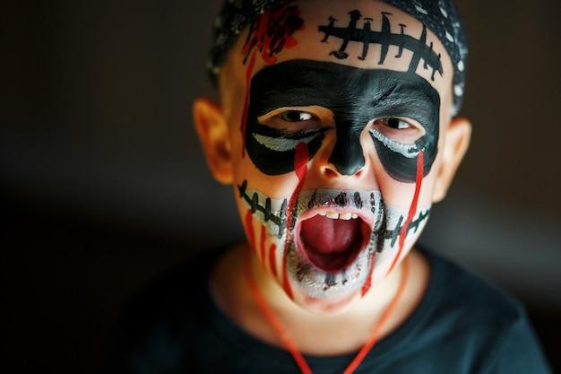 Emocional retrato de un niño gritando con un zombie aterrador en su rostro.