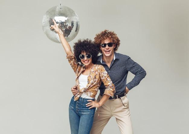 Emocional sonriente retro amorosa pareja bailando cerca de la bola de discoteca.