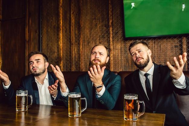 Emocionales y molestos jóvenes en trajes se sientan a la mesa en el bar. agitan las manos y miran hacia adelante. chicos ven el partido de fútbol.