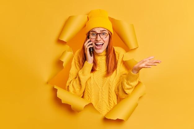 Emocionalmente molesta chica pelirroja que habla por teléfono levanta la palma de la mano y discute algo desagradable expresa emociones negativas exclama enojada rompe a través del agujero de papel