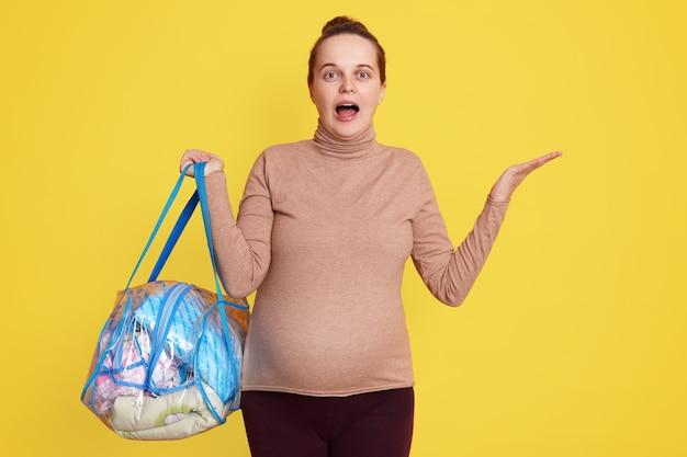 Emocionalmente sorprendida mujer embarazada prepara diferentes artículos para el recién nacido que va al hospital de maternidad, vistiendo ropa casual, sosteniendo el bolso, mira asombrada, extendiendo las manos a un lado.