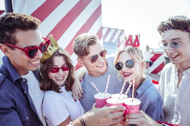 Emociones brillantes. jóvenes complacidos que expresan positividad mientras se divierten en la fiesta