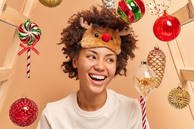 Emociones felices y estado de ánimo festivo. la mujer sincera positiva sonríe ampliamente expresa emociones positivas usa máscara de dormir de reno en la frente rodeada de juguetes de año nuevo pasa tiempo en casa acogedora.