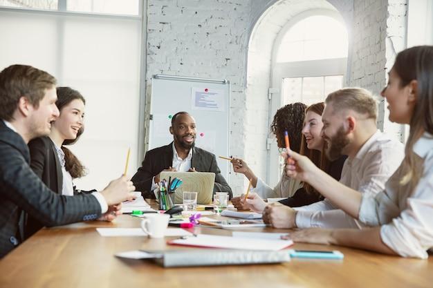 Emociones felices. grupo de jóvenes empresarios que tienen una reunión. grupo diverso de compañeros de trabajo discuten nuevas decisiones, planes, resultados, estrategia. creatividad, lugar de trabajo, negocios, finanzas, trabajo en equipo.