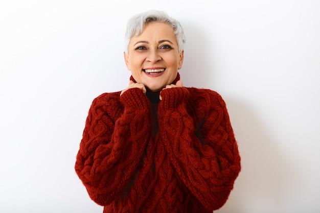 Emociones humanas positivas y percepción de la vida. hermosa mujer encantadora de pelo gris en retiro expresando una reacción sincera, con mirada feliz, fascinada con las buenas noticias, tomados de la mano en su rostro