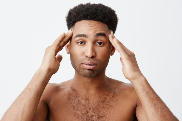 Emociones negativas. hombre que tiene dolor de cabeza después de ir de fiesta toda la noche. cerca del joven hombre de piel oscura con peinado afro sin ropa masajeando la cabeza con las manos.