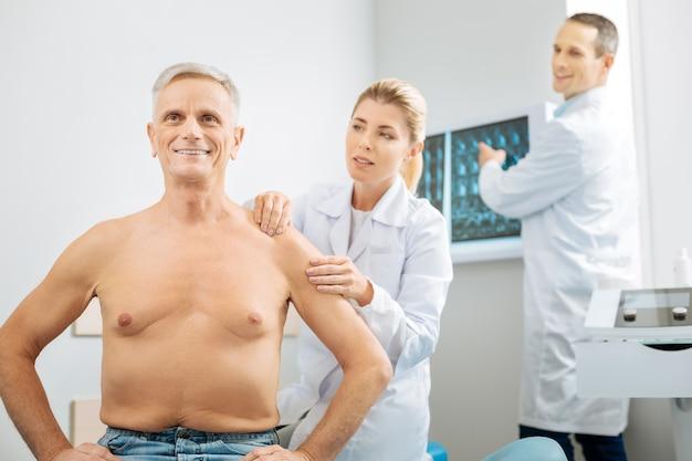 Emociones positivas. alegre agradable anciano sentado en el consultorio del médico y sonriendo mientras está lleno de energía