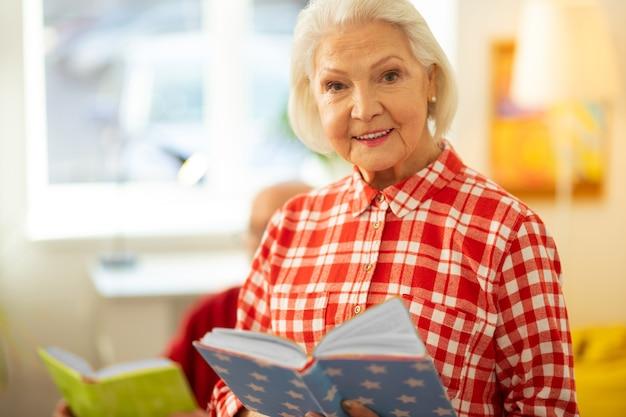 Emociones positivas. bonita mujer de pelo gris de muy buen humor mientras lee un libro interesante