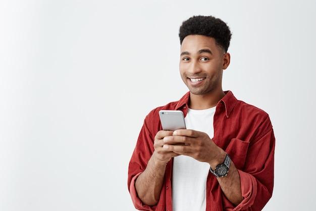 Emociones positivas. cerca de joven apuesto hombre de piel oscura con peinado afro en camiseta blanca y camisa roja sonriendo con dientes, conversando con un amigo en el teléfono inteligente