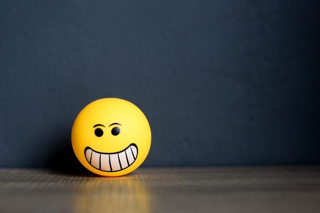Emoticon sonriente sobre fondo gris oscuro