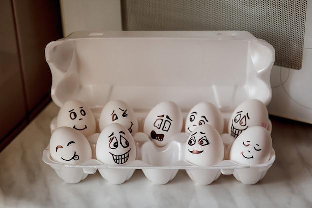 Emoticonos de huevos. pinturas y pincel de huevos sobre la mesa de la cocina.