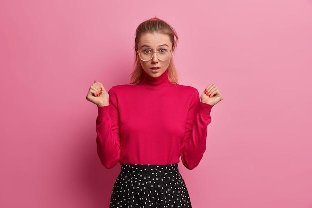 Emotiva hembra adulta joven retiene la respiración, oye algo asombroso, levanta la mano, no puede creer lo que ve, usa cuello alto y falda, ve algo asombrado