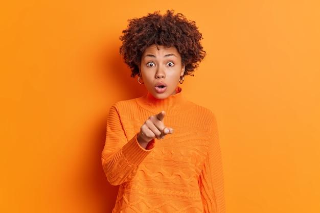 Emotiva mujer afroamericana con cabello rizado mira fijamente los ojos con errores indica directamente a la cámara retiene la respiración ve una oferta inesperada