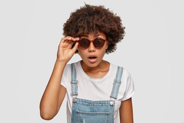 Emotiva mujer negra estupefacta con corte de pelo afro