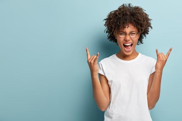 Emotiva mujer de piel oscura hace un letrero de rock n roll, dice que haré rock en esta fiesta, grita fuerte, usa anteojos redondos