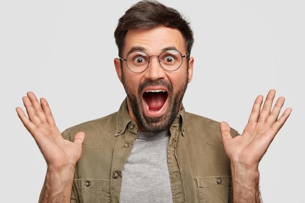 Emotivo sorprendido sorprendido feliz macho agarra las manos, abre la boca abierta y los ojos salieron, no puedo creer en un gran éxito, usa gafas redondas, vestido con una camisa de moda, aislado sobre una pared blanca