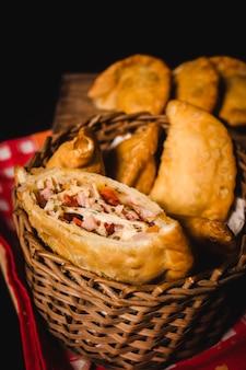 Una empanada napolitana abierta por la mitad, con un juego de empanadas encima de un mantel rojo.