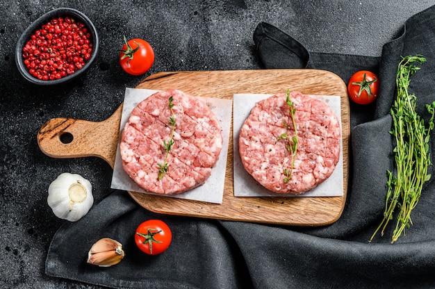 Empanada de pollo crudo, chuletas de carne picada en una tabla de cortar. carne picada orgánica. fondo negro. vista superior