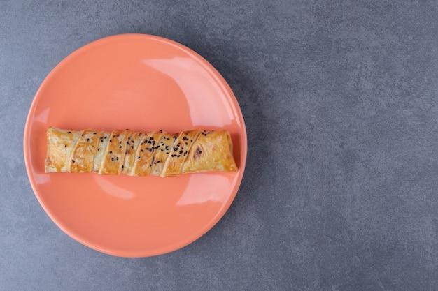 Empanada de sésamo en placa sobre mesa de mármol.