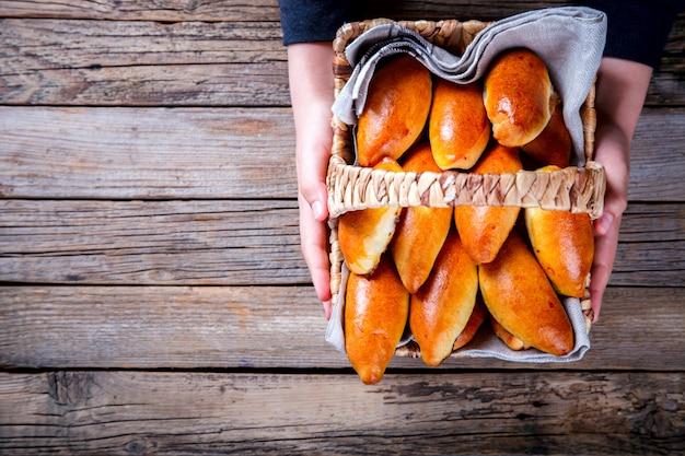 Empanadas en la canasta en manos de un niño. relleno de confitura de bayas y frutas. se lleva a casa. postre. copie espacio para texto