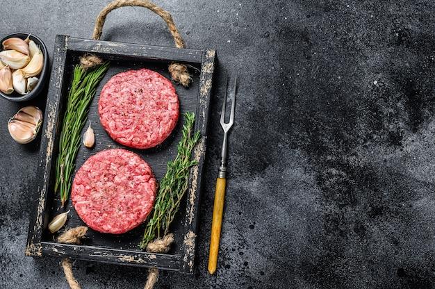 Empanadas de carne de res cruda para hamburguesas de carne molida y hierbas en una tabla de madera