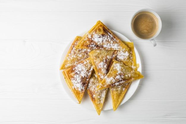 Empanadas caseras en un plato y una taza de café
