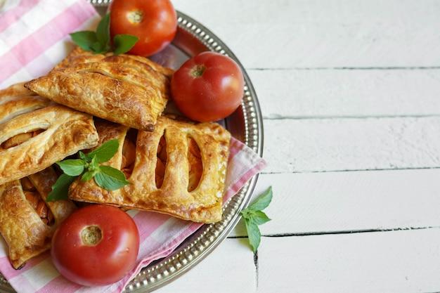 Empanadas de hojaldre con pesto rojo y menta en mesa de madera con lugar para texto