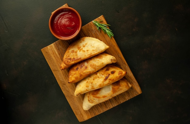 Empanadas latinoamericanas fritas con salsa de tomate con copia espacio para su texto