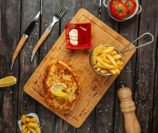 Empanadas de pechuga de pollo adornadas con limón, servidas con papas fritas, mayonesa y salsa de tomate