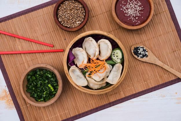 Empanadillas con ensalada en vapor de bambú rodeadas de cebollino; semillas de cilantro y palillos en mantel