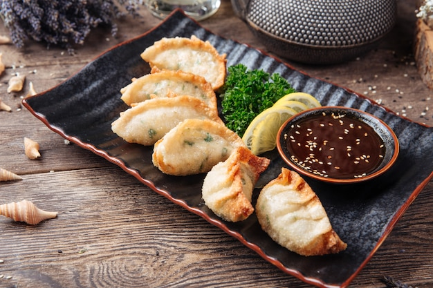 Empanadillas japonesas fritas salsa de gedza mesa de madera