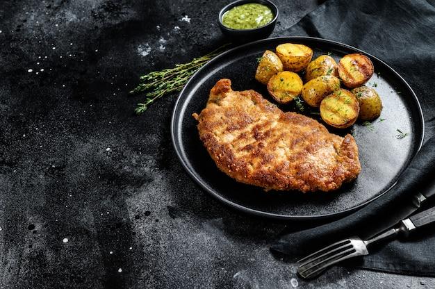 Empanizado alemán weiner schnitzel con patatas. fondo negro. vista superior. copia espacio