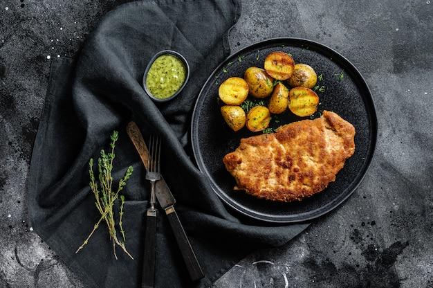 Empanizado alemán weiner schnitzel con patatas. .