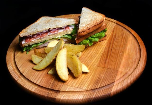 Emparedado con las patatas cocidas al horno en un tablero de madera aislado en el fondo blanco. comida restaurada. comida rápida.