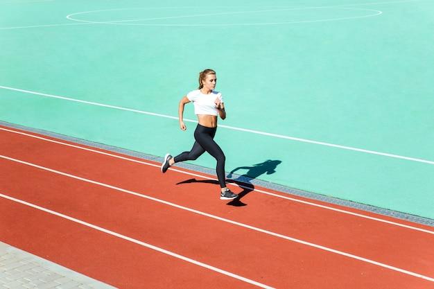 Emparejador de mujer joven corriendo en el estadio
