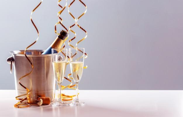 Empareje una copa de champán con una botella en un recipiente de metal. celebración de año nuevo