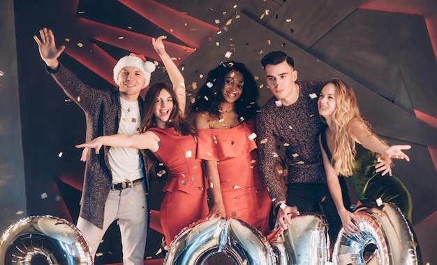 Empecemos la fiesta. grupo de hermosas jóvenes amigos con números inflables en manos celebrando el nuevo año 2019