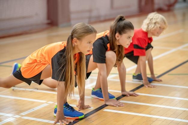 Empezar juego. niños en ropa deportiva brillante esperando para comenzar el juego.