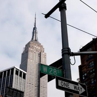 Empire state building y señales de la calle en manhattan, nueva york, estados unidos