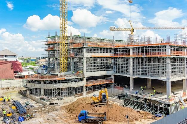 Emplazamiento de la obra y edificio de gran altura sin terminar con andamios.