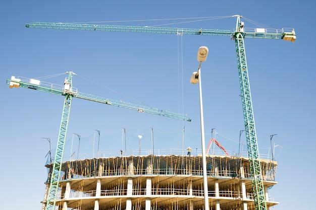 Emplazamiento de la obra con grúa y edificio contra el cielo azul