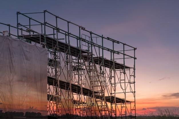 Emplazamiento de la obra con la torre del andamio y edificio con el fondo de la puesta del sol
