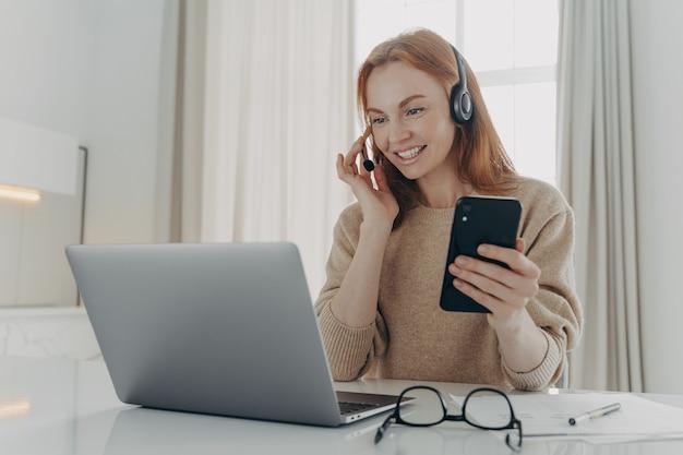 Empleada en auriculares tiene videoconferencia tiene teléfono inteligente moderno