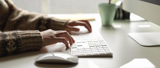 Empleada escribiendo en el teclado de la computadora en el escritorio de oficina mínima con agenda y taza