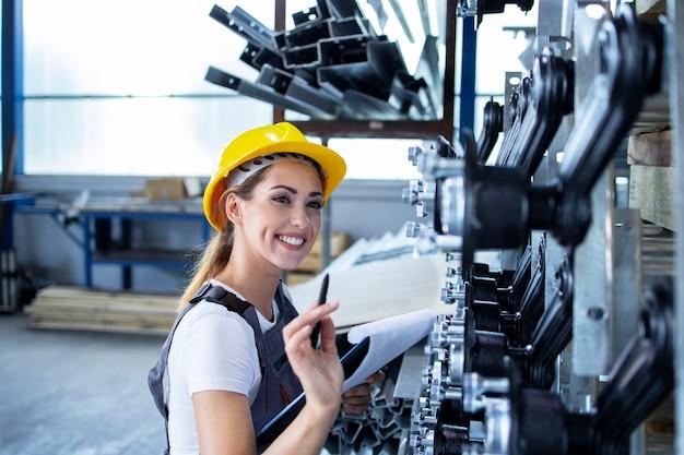 Empleada industrial femenina en uniforme de trabajo y casco comprobando la producción en la fábrica.