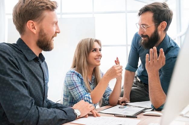 Empleada joven a sus colegas explicando sus ideas, trabajo en equipo