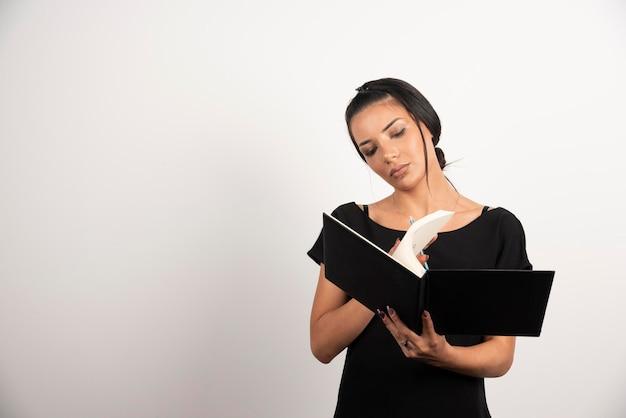 Empleada mirando notas sobre la pared blanca.