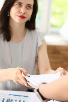 Empleada muestra paquete de documentos al gerente