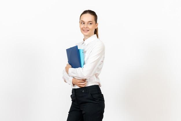 Empleada de oficina en blusa blanca sosteniendo documentos con sonrisa en blanco